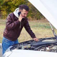 discontented man talking on the phone and looking under the hood of breakdown car at outdoor